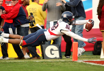 LOS ANGELES, CA - DECEMBER 05:  Wide receiver Juron Criner #82 of the Arizona Wildcats dives into the end zone with  a 36 yard catch for the winning touchdown in the fourth quarter against the USC Trojans on December 5, 2009 at the Los Angeles Coliseum in