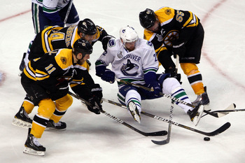 BOSTON, MA - JUNE 06:  Daniel Sedin #22 of the Vancouver Canucks loses his balance while handling the puck against Johnny Boychuk #55, Gregory Campbell #11 and Dennis Seidenberg #44 of the Boston Bruins during Game Three of the 2011 NHL Stanley Cup Final