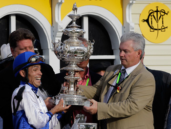 BALTIMORE, MD - MAY 21:  Jockey Jesus Castanon (L) and co-owner Mike Lauffer (R) hold the trophy in the winners circle after their horse Shackleford won the 136th running of the Preakness Stakes at Pimlico Race Course on May 21, 2011 in Baltimore, Marylan