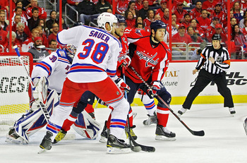 WASHINGTON , DC - APRIL 23: Brooks Laich #21 and Alex Ovechkin #8 of the Washington Capitals battle in the crease against Michael Sauer #38 and Henrik Lundqvist #30 of the New York Rangers in Game Five of the Eastern Conference Quarterfinals during the 20