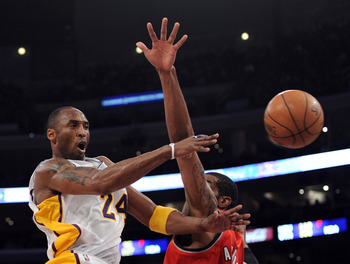 LOS ANGELES, CA - MARCH 20:  Kobe Bryant #24 of the Los Angeles Lakers makes a pass around LaMarcus Aldridge #12 of the Portland Trail Blazers at the Staples Center on March 20, 2011 in Los Angeles, California.  NOTE TO USER: User expressly acknowledges a