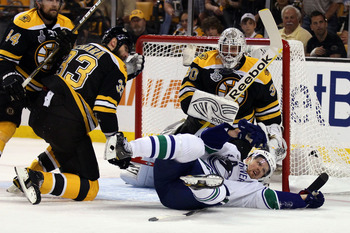 BOSTON, MA - JUNE 08:  Henrik Sedin #33 of the Vancouver Canucks falls over Zdeno Chara #33 of the Boston Bruins during Game Four of the 2011 NHL Stanley Cup Final at TD Garden on June 8, 2011 in Boston, Massachusetts.  (Photo by Elsa/Getty Images)