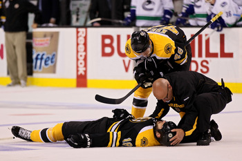 A Boston Bruins trainer and David Krejci (46) attend to an injured Nathan Horton in Game 3 of the Stanley Cup Finals