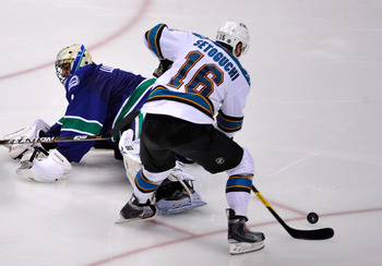 VANCOUVER, CANADA - MAY 24:  Devin Setoguchi #16 of the San Jose Sharks plays the puck past goaltender Roberto Luongo #1 of the Vancouver Canucks and goes on to score into an empty net in the third period  in Game Five of the Western Conference Finals dur