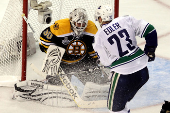 Tim Thomas stops this scoring attempt by Vancouver's Alex Edler