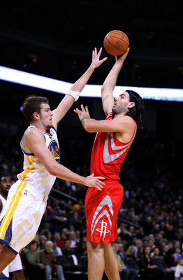 OAKLAND, CA - DECEMBER 20:  Luis Scola #4 of the Houston Rockets shoots over David Lee #10 of the Golden State Warriors at Oracle Arena on December 20, 2010 in Oakland, California. NOTE TO USER: User expressly acknowledges and agrees that, by downloading