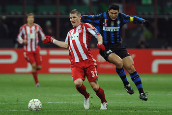 MILAN, ITALY - FEBRUARY 23:  Javier Zanetti of Inter Milan clashes with Bastian Schweinsteiger of FC Bayern Muenchen during the UEFA Champions League round of 16 first leg match between Inter Milan v FC Bayern Muenchen on February 23, 2011 in Milan, Italy
