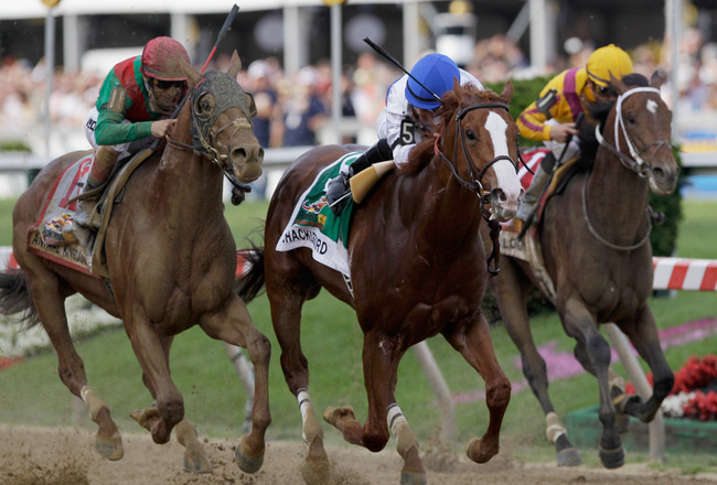 BALTIMORE, MD - MAY 21:  Jockey Jesus Castanon guides Shackleford #5 to victory over Animal Kingdom and jocky John Velazquez #11 (L) and Astrology with jockey Mike Smith #1 (R) to win the 136th running of the Preakness Stakes at Pimlico Race Course on May