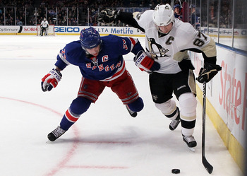 NEW YORK - MARCH 04:  Sidney Crosby #87 of the Pittsburgh Penguins tries to control the puck against Chris Drury #23 of the New York Rangers on March 4, 2010 at Madison Square Garden in New York City. The Penguins defeated the Rangers 5-4 in overtime.  (P