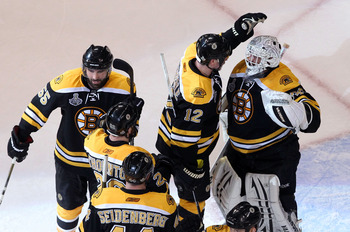 BOSTON, MA - JUNE 08:  Tim Thomas #30 of the Boston Bruins celebrates with his teammates Dennis Seidenberg #44, Johnny Boychuk #55 and Tomas Kaberle #12 after defeating the Vancouver Canucks in Game Four of the 2011 NHL Stanley Cup Final at TD Garden on J