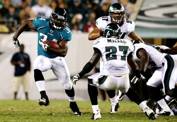 PHILADELPHIA, PA - AUGUST 27:  Chauncey Washington #34 of the Jacksonville Jaguars runs the ball against Quinton Mikell #27 of the Philadelphia Eagles during the preseason game at Lincoln Financial Field on August 27, 2009 in Philadelphia, Pennsylvania.