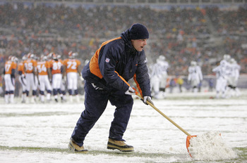 DENVER - NOVEMBER 28:  A member of the grounds crew shovels snow off a yard line during the game between the Oakland Raiders and the Denver Broncos on November 28, 2004 at Invesco Field at Mile High Stadium in Denver, Colorado.  The Raiders won 25-24.  (P