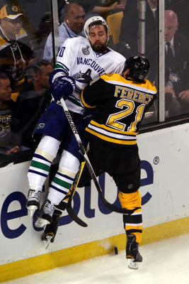 Boston Bruin Andrew Ference takes Vancouver's Chris Higgins out of the play
