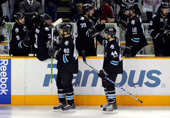 SAN JOSE, CA - MAY 22:  Kent Huskins #40 and Marc-Edouard Vlasic #44 of the San Jose Sharks skate by the Sharks bench to celebrate a goal by Vlasic in the third period in Game Four of the Western Conference Finals during the 2011 Stanley Cup Playoffs at H