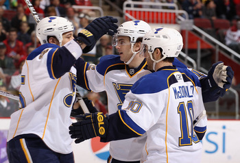 GLENDALE, AZ - MARCH 22:  Kevin Shattenkirk #12 (C) of the St. Louis Blues celebrates with teammates Chris Stewart #25 and Andy McDonald #10 after Shattenkirk scored a first period goal against the Phoenix Coyotes during the NHL game at Jobing.com Arena o