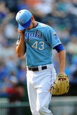 KANSAS CITY, MO - JUNE 9:  Aaron Crow #43 of the Kansas City Royals wipes his face as he walks back to the dugout following the eight inning against the Toronto Blue Jays at Kauffman Stadium on June 9, 2011 in Kansas City, Missouri. The Royals defeated th