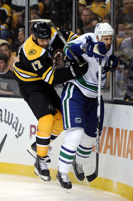 BOSTON, MA - JUNE 08:  Milan Lucic #17 of the Boston Bruins checks Andrew Alberts #41 of the Vancouver Canucks during Game Four of the 2011 NHL Stanley Cup Final at TD Garden on June 8, 2011 in Boston, Massachusetts.  (Photo by Harry How/Getty Images)