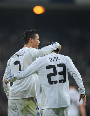 MADRID, SPAIN - JANUARY 13:  Mesut Ozil of Real Madrid celebrates with Cristiano Ronaldo after scoring Real's third goal during the Copa del Rey quarter final first leg match between Real Madrid and Atletico Madrid at Estadio Santiago Bernabeu on January