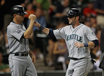 CHICAGO, IL - JUNE 08: Jack Wilson #2 of the Seattle Mariners (L) congratulates teammate Adam Kennedy #4 after both scored runs in the 10th inning against the Chicago White Sox at U.S. Cellular Field on June 8, 2011 in Chicago, Illinois. The Mariners defe