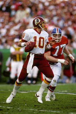 SAN DIEGO - JANUARY 31:  Quarterback Jay Schroeder #10 of the Washington Redskins drops back to pass under pressure from defensive end Karl Mecklenburg #77 of the Denver Broncos during Super Bowl XXII at Jack Murphy Stadium on January 31, 1988 in San Dieg