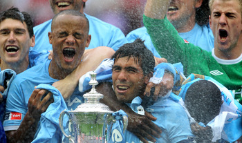 LONDON, ENGLAND - MAY 14:  Carlos Tevez of Manchester City and his team mates celebrate with the trophy after they won the FA Cup sponsored by E.ON Final match between Manchester City and Stoke City at Wembley Stadium on May 14, 2011 in London, England.