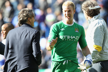BOLTON, ENGLAND - MAY 22: Joe Hart (C) of Manchester City enjoys his sides 2-0 victory with manager Roberto Mancini (L) during the Barclays Premier League match between  Bolton Wanderers and Manchester City at the Reebok Stadium on May 22, 2011 in Bolton,