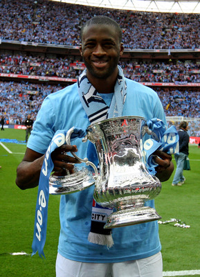 LONDON, ENGLAND - MAY 14:  Yaya Toure holds the trophy after he and his Manchester City team mates won the FA Cup sponsored by E.ON Final match between Manchester City and Stoke City at Wembley Stadium on May 14, 2011 in London, England.  (Photo by Alex L
