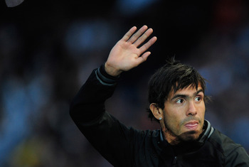 MANCHESTER, ENGLAND - MAY 23:  Carlos Tevez of Manchester City waves to the fans during the Manchester City FA Cup Winners Parade at the City of Manchester stadium on May 23, 2011 in Manchester, United Kingdom.  (Photo by Jamie McDonald/Getty Images)