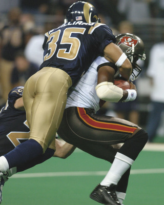 Tampa Bay Buccaneers wide receiver Tim Brown grabs a fourth-quarter pass  as St. Louis Rams safety Aeneas Williams defends  October 18, 2004 at the Edward Jones Dome in St. Louis.  The Rams defeated the Bucs  28 to 21 in a Monday Night Football game on AB