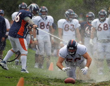 ENGLEWOOD, CO - AUGUST 05:  Lonie Paxton #66 hoses down offensive lineman J.D. Walton #50 of the Denver Broncos as dives into the mud as rookies partake in the slip and slide fumble drill during training camp at Dove Valley on August 5, 2010 in Englewood,