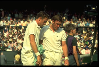 1970's:  JOHN NEWCOMBE (LEFT) AND TONY ROCHE OF AUSTRALIA DISCUSS TACTICS DURING A BREAK IN A DOUBLES MATCH AT THE WIMBLEDON TENNIS CHAMPIONSHIPS.