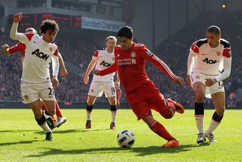 LIVERPOOL, ENGLAND - MARCH 06:  Luis Suarez of Liverpool goes clear of Chris Smalling and Rafael (L) of Manchester United to set up the first goal during the Barclays Premier League match between Liverpool and Manchester United at Anfield on March 6, 2011
