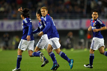 OSAKA, JAPAN - MARCH 29: Yasuhito Endo (L) of Japan celebrates after scoring the first goal with Keisuke Honda and Yuto Nagatomo during a charity match for those affected by the earthquake and tsunami at Nagai Stadium on March 29, 2011 in Osaka, Japan. (P