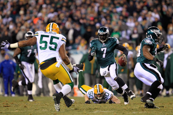 PHILADELPHIA, PA - JANUARY 09:  Michael Vick #7 of the Philadelphia Eagles scrambles against A.J. Hawk #50 and Desmond Bishop #55 of the Green Bay Packers during the 2011 NFC wild card playoff game at Lincoln Financial Field on January 9, 2011 in Philadel