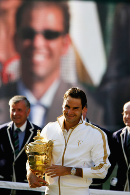 WIMBLEDON, ENGLAND - JULY 05:  Roger Federer of Switzerland celebrates with the trophy as Peter Sampras is shown on the screen after the men's singles final match against Andy Roddick of USA on Day Thirteen of the Wimbledon Lawn Tennis Championships at th