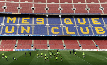 BARCELONA, SPAIN - APRIL 05:  FC Barcelona players practice backdropped by the words 'More than a club' written in the stands during a training session ahead of their UEFA Champions League quarter final second leg match against Arsenal at the Camp Nou sta
