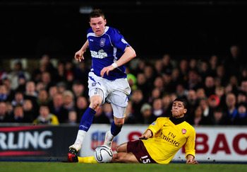 IPSWICH, ENGLAND - JANUARY 12: Connor Wickham of Ipswich Town is challenged by Denilson of Arsenal during the Carling Cup Semi Final First Leg match between Ipswich Town and Arsenal at Portman Road on January 12, 2011 in Ipswich, England.  (Photo by Jamie