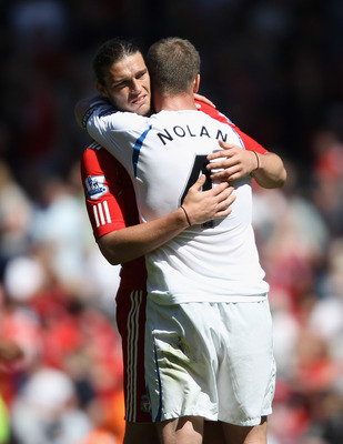 LIVERPOOL, ENGLAND - MAY 01:  Andy Carroll of Liverpool hugs Kevin Nolan of Newcastle United at the final whistle of the Barclays Premier League match between Liverpool  and Newcastle United at Anfield on May 1, 2011 in Liverpool, England.  (Photo by Cliv