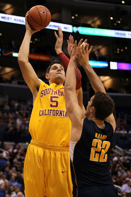 LOS ANGELES, CA - MARCH 10:  Nikola Vucevic #5 of the USC Trojans shoots over Harper Kamp #22 of the California Golden Bears in the second half in the quarterfinals of the 2011 Pacific Life Pac-10 Men's Basketball Tournament at Staples Center on March 10,