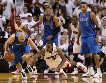 MIAMI, FL - JUNE 12:  Jason Kidd #2 of the Dallas Mavericks controls a loose ball against Mario Chalmers #15 of the Miami Heat in Game Six of the 2011 NBA Finals at American Airlines Arena on June 12, 2011 in Miami, Florida. The Mavericks won 105-95. NOTE
