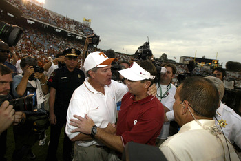 DALLAS - OCTOBER 11:  Head coach Mack Brown of the Texas Longhorns and Bob Stoops of the Oklahoma Sooners greet each other at the end of the game at the Cotton Bowl on October 11, 2003 in Dallas, Texas.  The Sooners defeated the Longhorns 65-13.  (Photo b