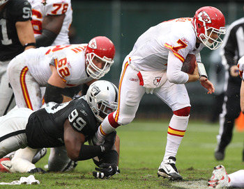 OAKLAND, CA - NOVEMBER 07:  Matt Cassel #7 of the Kansas City Chiefs runs with the ball against Lamarr Houston #99 of the Oakland Raiders during an NFL game at Oakland-Alameda County Coliseum on November 7, 2010 in Oakland, California.  (Photo by Jed Jaco