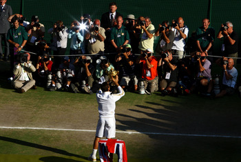 WIMBLEDON, ENGLAND - JULY 05:  Roger Federer of Switzerland poses for photographers as he celebrates victory with the trophy after the men's singles final match against Andy Roddick of USA on Day Thirteen of the Wimbledon Lawn Tennis Championships at the