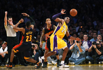 LOS ANGELES, CA - DECEMBER 29:  Kobe Bryant #24 of the Los Angeles Lakers goes for a loose ball in front of Monta Ellis #8 and C.J. Watson #23 of the Golden State Warriors on December 29, 2009 at Staples Center in Los Angeles, California.  The Lakers won
