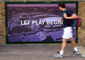 LONDON, ENGLAND - JUNE 28:  A visitor walks past a poster on Day Seven of the Wimbledon Lawn Tennis Championships at the All England Lawn Tennis and Croquet Club on June 28, 2010 in London, England.  (Photo by Oli Scarff/Getty Images)