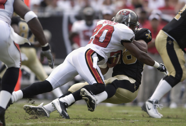TAMPA BAY, FL - SEPTEMBER 8:  Cornerback Ronde Barber #20 of the Tampa Bay Buccaneers applies a big hit to an unidentified New Orleans Saint during the first quarter on September 8, 2002 at Raymond James Stadium in Tampa, Florida.  The Saints defeated the