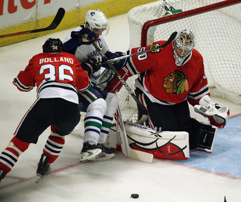 CHICAGO, IL - APRIL 24: Dave Bolland #36 of the Chicago Blackhawks knocks down Henrik Sedin #33 of the Vancouver Canucks as Corey Crawford #50 rejects a shot in Game Six of the Western Conference Quarterfinals during the 2011 NHL Stanley Cup Playoffs at t
