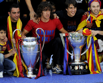 BARCELONA, SPAIN - MAY 29:  FC Barcelona players pose with the La Liga Tropy and the UEFA Champions League trophy during the celebrations after winning the UEFA Champions League Final against Manchester United at Camp Nou Stadium on May 29, 2011 in Barcel