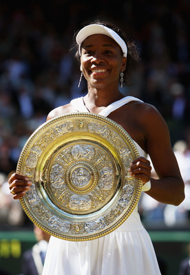 LONDON - JULY 05:  Venus Williams of United States celebrates winning the Championship trophy during the women's singles Final match against Serena Williams of United States on day twelve of the Wimbledon Lawn Tennis Championships at the All England Lawn