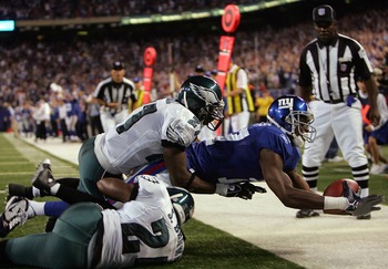 EAST RUTHERFORD, NJ - SEPTEMBER 30:  Plaxico Burress #17 of the New York Giants goes with a touchdown catch over Sheldon Brown #24 and Quintin Mikell  #27 of the Philadelphia Eagles at Giants Stadium on September 30, 2007 in East Rutherford, New Jersey.